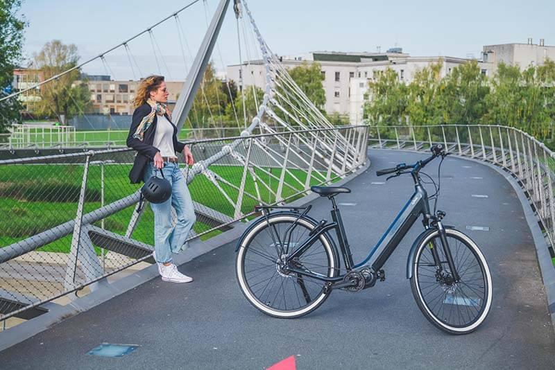 A woman in front of an O2feel e-bike on a bridge